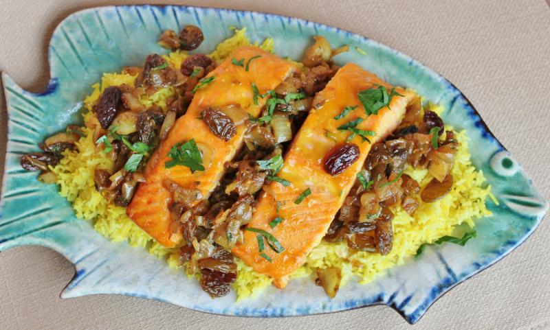 Yellow rice with fish and pomegranate raisin sauce